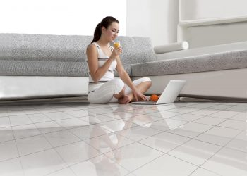 woman sitting on tiled floor with laptop